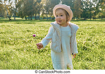 Child girl walking in the park with clover in hand