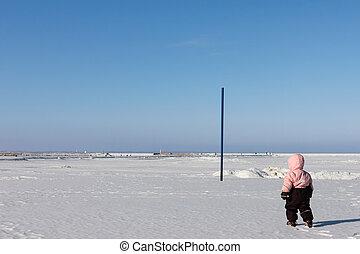 Child girl walks on snow