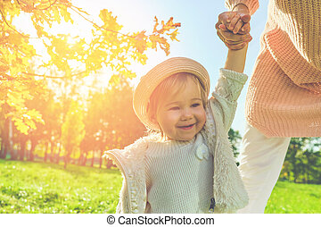 Child girl walks with her mother in the park in rustic clothes