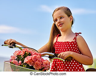 Child girl wearing polka dots dress rides bicycle into park.