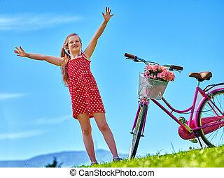 Child girl wearing red polka dots dress rides bicycle . - ...