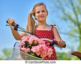 Child girl wearing red polka dots dress rides bicycle.