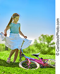 Child girl wearing red polka dots dress rides bicycle into park.