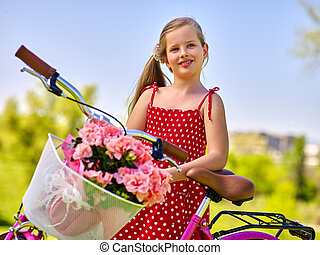 Child girl wearing red sundress rides bicycle into park.