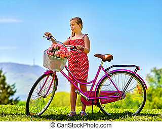 Child girl wearing sundress rides bicycle into park.