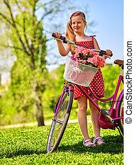 Child girl wearing white polka dots dress rides bicycle .