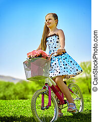Child girl wearing white polka dots dress rides bicycle into park.