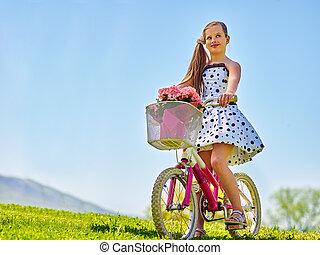 Child girl wearing white polka dots dress rides bicycle park.