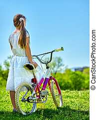 Child girl wearing white skirt rides bicycle into park. - ...