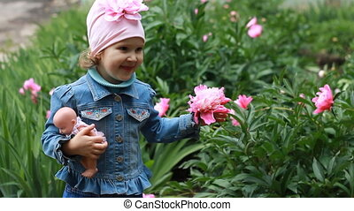 Child girl with a doll sniffs the aroma of peony flowers.
