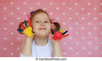 Child girl with dirty hands in multicolored paint. Happy baby and painting.