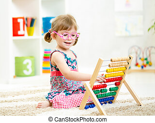 child girl with eyeglasses playing abacus toy - kid girl...