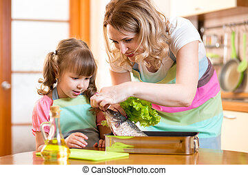 child girl with mom cooking fish in the kitchen