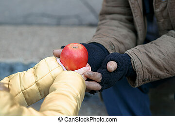 Child gives apple to the beggar.