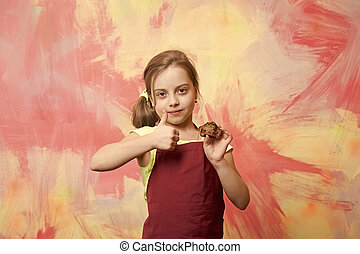 Child giving thumbs up gesture to cake.