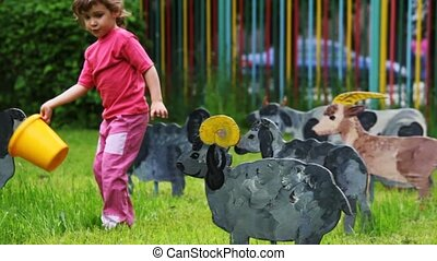 child goes on lawn and feed from bowls drawn silhouette of nanny-goat