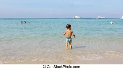 Small child carefully walks along shore and enters sea. Yachts are visible on horizon.