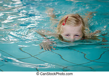child half underwater in swimming pool