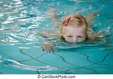 child half underwater in swimming pool