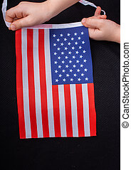 Child hand holding an American flag in hand