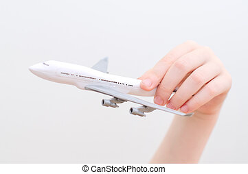 Child hand holding model airplane.