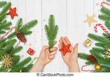 Child hand with on wooden background decorated christmas accessories.