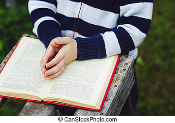 Child hands are on folded in prayer on a Holy Bible. Concept for faith, spirituality and religion.