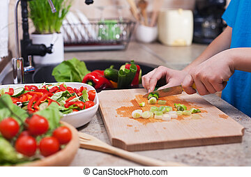 Child hands chopping vegetables on cutting board - the spring onions