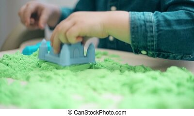 Child hands close-up destroys the castle of kinetic sand,HD...