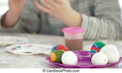 Child hands decorating easter eggs