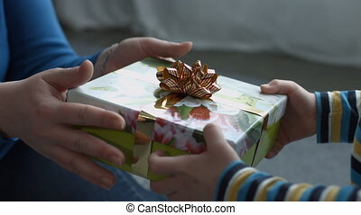 Child hands giving holiday gift box to his mother