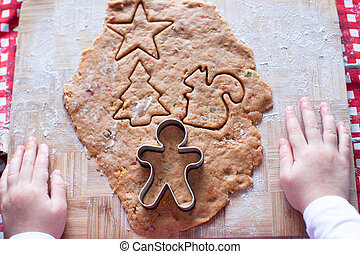 Child hands making from dough gingerbread man for Christmas