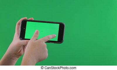 Child hands using a smart phone. chroma key, green screen