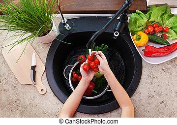 Child hands washing vegetables at the kitchen sink