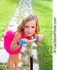child happy girl playing with scooter in garden