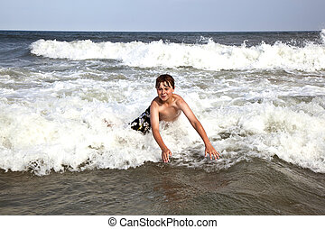 child has fun in the waves of the ocean