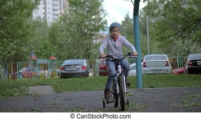 Child having active outdoor leisure with riding a bike