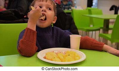 Child having dinner in food court cafe