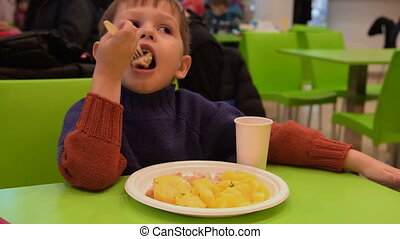 Child having dinner in food court cafe