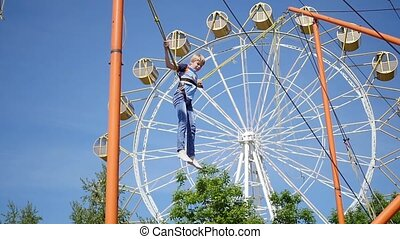 child having fun at an amusement Park.Jumping on a trampoline. Family holiday in the park