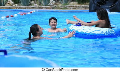 Portrait of a young girls and boy having fun at the pool during summer holiday