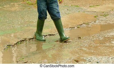 child having fun in rubber boots in a puddle - The boy found...
