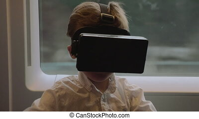 Child having fun in the train with VR glasses