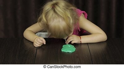 Child having fun making green slime. Kid playing with hand made toy slime