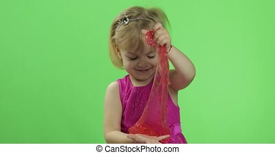Child having fun making red slime. Kid playing with hand...