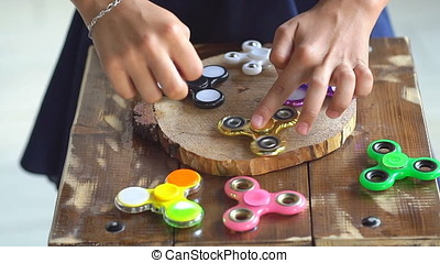 Child having fun outdoors with Spinner, slow motion. Young caucasian girl showing skills by flicking spinners with finger in the summer park.
