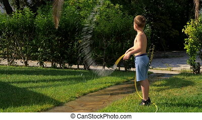 Child having fun when watering lawn with hose - Boy playing...