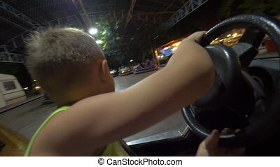 Child having fun with driving bumper car at fun fair - ...