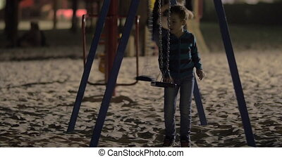 Child having fun with empty swings on playground in the evening