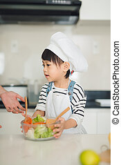 Child helping mother cooking in modern kitchen